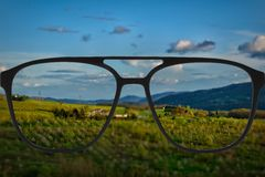 Clear image in glasses against blurry landscape Royalty Free Stock Photography