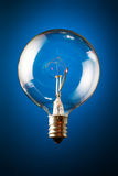 Clear incandescent bulb. Edison's round incandescent bulb on blue gradient background royalty free stock photo