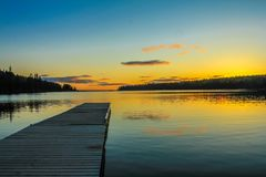 Clear Lake, Riding Mountain National Park, Manitoba, Canada. Sun set starts as you follow along the pier into clear lake Royalty Free Stock Photo