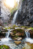 Mountain waterfall. Clear mountain stream flows down from the mountains. Rocks around are covered with moss. Sunny day Stock Images