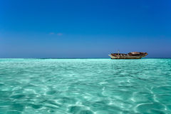 Clear ocean maldives water under blue sky with abandoned boat Royalty Free Stock Photos