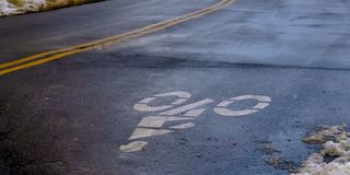 Clear Panorama Bicycle lane sign painted on a winter road in Utah stock images
