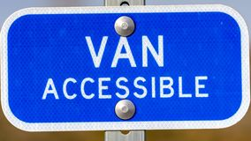 Clear Panorama Blue sign with a Van Accessible text on a parking area for handicapped people royalty free stock photography