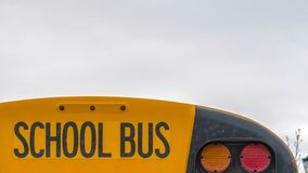 Clear Panorama Close up of the back side of a yellow school bus against homes and cloudy sky. The rear glass window of the bus also serves as an emergency exit stock photography