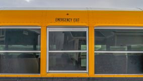 Clear Panorama CLose up of the exterior of a yellow school bus against cloudy sky. One of the windows serves as an exit for the passengers in case of an stock image