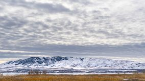Clear Panorama Dramatic sky filled with cottony clouds over a scenic landscape in winter. A lake and snow capped mountain cna be seen beyond the vast grassy stock images