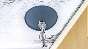 Clear Panorama Exterior view of a home with a small satellite dish at the corner of the roof. The roof shingles are covered with fresh snow this winter season royalty free stock photos
