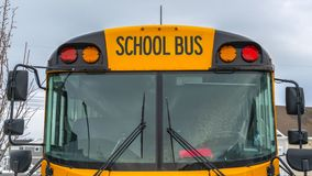 Clear Panorama Front view of a yellow school bus with homes and cloudy sky in the background. Several side mirros and signal lights can be seen at the front of royalty free stock images
