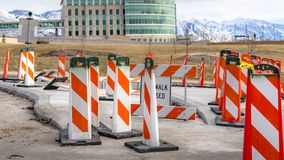 Clear Panorama Sidewalk Closed sign and road safety poles on a paved road under repair. In the background is a modern building with skybridge and snowy stock photos