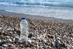 Clear plastic bottle of water on the beach with a sea  view Royalty Free Stock Image