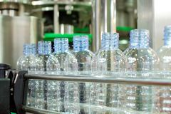 Clear plastic bottles on the conveyor belt of industrial machinery. Selective focus a row of clear plastic bottles on the conveyor belt of industrial machinery stock photos