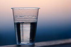 Clear Plastic Cup on Gray Surface Royalty Free Stock Photos