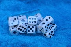 Clear plastic cup with white dice on a blue wool fabric royalty free stock photos