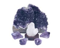 Clear quartz cluster surrounded by amethyst purple druse geode and amethyst points Stock Images