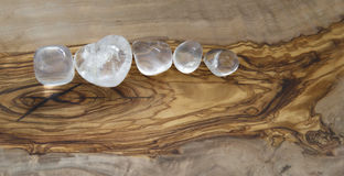 Clear quartz crystals on olive wood background. Five different shaped clear healing crystals on a flat smooth olive wood background Stock Image
