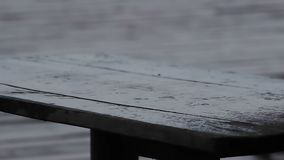 Clear raindrops falling down on wooden table. Sad and rainy weather, bad mood