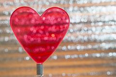 Clear Red Heart On Coil Spring. Metallic Foil Background With Angled Silver Shiny Stripes, Orange Highlights. Valentines Day,. Christmas, New Year Banner royalty free stock image