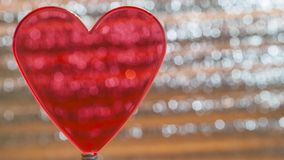 Clear Red Heart On Coil Spring. Metallic Foil Background With Angled Silver Shiny Stripes, Orange Highlights. Valentines Day,. Christmas, New Year Banner royalty free stock images