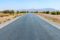 Clear road in Moroccan desert. Nobody. Mountains on horizon Stock Photography