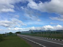 Clear road. A shot of an empty road by the airport runaway track. The shot was taken near Langkawi airport in Kedah, Malaysia Royalty Free Stock Photography