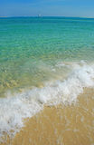 Clear Sea, Smooth Sailing. Crystal clear ocean surf with sailboat in distance Stock Images