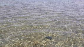 Clear sea water off the coast. The sandy bottom is clearly visible through the water stock footage