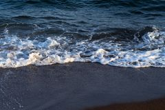 Clear sea water tide on dark volcanic beach. Relaxing sea wave surf over seashore. Royalty Free Stock Photo