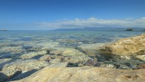 Clear sea water is washing gravel on coast, close-up view with horizon in background. Landscape with sea stock video