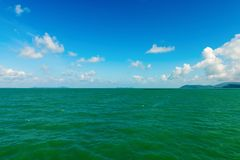 Seascape with green islands on horizon. Clear seascape with green islands on horizon and white clouds on the blue sky Royalty Free Stock Images