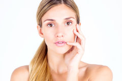 Clear skin. Beautiful woman looks at the camera and touching fac Royalty Free Stock Image