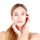 Clear skin. Beautiful woman looks at the camera and touching fac Royalty Free Stock Photos