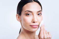 Cheerful woman carrying out skincare routine and smiling Royalty Free Stock Photo