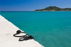 Clear sky, azure blue sea, and concrete pier, with black rope in Greece. Stock Image