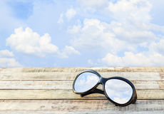 Clear sky in eyeglasses on the wooden background Stock Photo