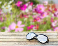 Clear sky in eyeglasses on the wooden table over blurred background Stock Image