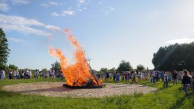 Clear sky in good spring weather, summer festivities near bonfire on open air, many of people walk around bright fire stock footage