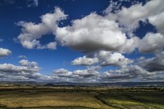 Clear sky with natural colors of an intense Mediterranean blue and white clouds on a plain of typical Sardinian vegetation stock image