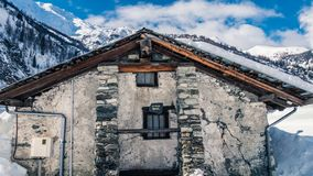 House is snowed in under a thick layer of snow. Clear sky`s above wild enormous mountains on a winters day royalty free stock images