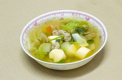 Clear soup with bean curd and minced pork in dish on cardboard b Royalty Free Stock Photos