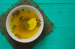 Clear soup with vegetables in plate on wooden table .Rustic styl Royalty Free Stock Photo