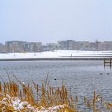 Clear Square Buildings against sky on a snow covered landscape beyond the lake in winter. Snowy wooden decks can also be seen above the water with grasses in stock image