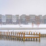 Clear Square Deck on a lake overlooking buildings in Daybreak. Snowy wooden deck on a lake in Daybreak, Utah viewed in winter. Buildings against gloomy sky can stock photography