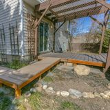 Clear Square Exterior of a home with a wooden walkway and deck on the yard. A pergola is constructed over the deck with a reflective glass door that leads stock image