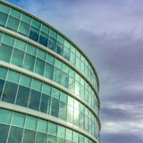 Clear Square Exterior view of a modern office building with reflective glass wall. A dramatic sky filled with gray clouds can be seen over the building royalty free stock images