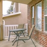Clear Square Front porch of a home with table and chairs in front of brick wall and window. The outdoor scenery is reflected on the sidelight that flanks the royalty free stock images