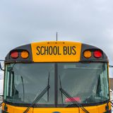 Clear Square Front view of a yellow school bus with homes and cloudy sky in the background. Several side mirros and signal lights can be seen at the front of royalty free stock images
