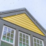 Clear Square Home with yellow wall and glass windows against cloudy sky in Daybreak Utah. The roof is covered with a sheet of fresh snow during winter season royalty free stock images