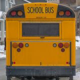 Clear Square Rear of a yellow school bus against snowy homes and cloudy sky in winter. A rectangular window and several signal lights can be seen at the back stock images