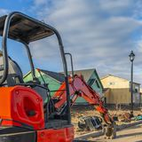 Clear Square Red excavator on a construction site for new homes against cloudy blue sky stock image