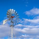 Clear Square Shiny steel windpump against a vibrant blue sky with cottony clouds royalty free stock photography